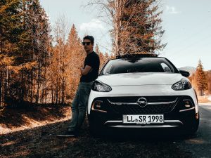 man leaning on white Opel car