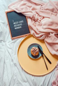 muffin beside knife and fork on saucer beside blanket