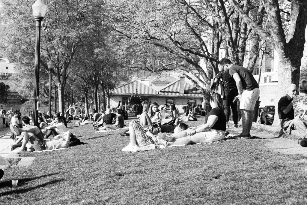 grayscale photo of people sitting on grass field