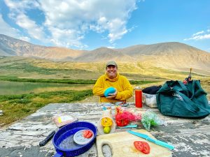 man in yellow crew neck t-shirt sitting on ground near mountain during daytime