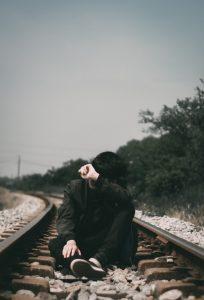 man in black jacket sitting on train rail during daytime