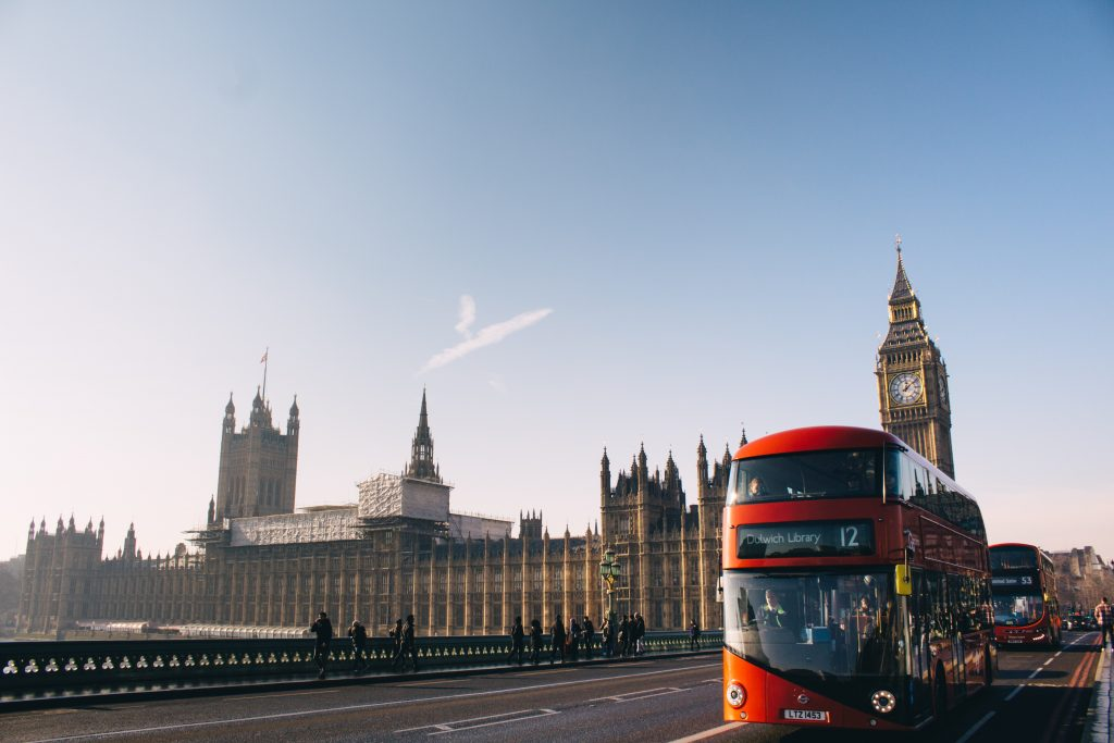 red double-decker bus passing Palace of Westminster, London during daytime