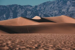 brown sand near snow covered mountain during daytime