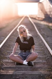 woman in black crew neck t-shirt and blue denim shorts sitting on train rail during