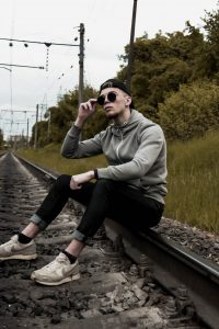 man in gray jacket and black pants sitting on train rail